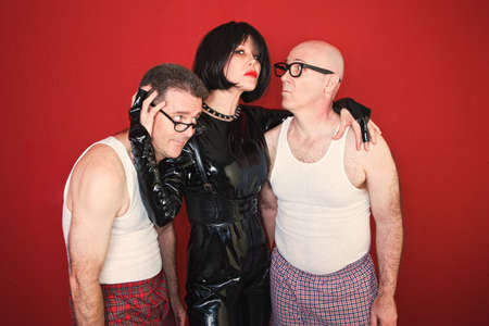 Confident dominatrix holds two insecure men around her.
