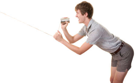 Skinny Caucasian man speaks on tin can phone over white background Stock Photo - 10553295