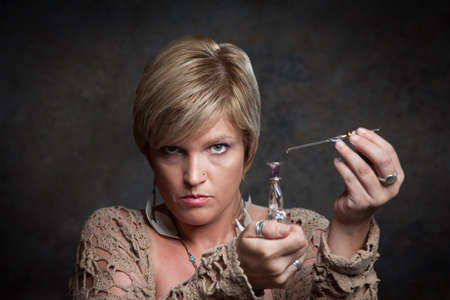 Woman uses a dropper to extract potion from bottle photo