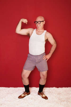 dweeb: Funny bald muscular man shows off his biceps ove rmaroon background