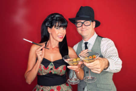 Happy Caucasian couple enjoy martini and cigarette over maroon background Stock Photo - 10553339