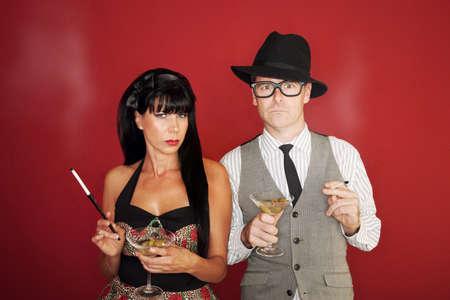 Suspicious Caucasian couple hold martini and cigarette Stock Photo - 10553397