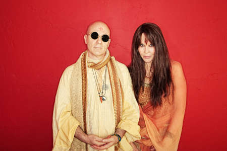 Bald Guru meditates with partner over maroon background