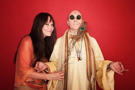 guru: Giggling woman with peacock feather tickles a meditating guru