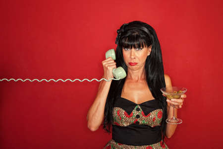 Upset Caucasian lady on phone with martini over maroon background photo