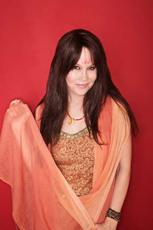cultural clothing: Smiling Hippy in Indian attire over maroon background Stock Photo