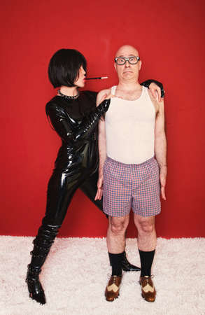 Dominatrix woman tightly grips a scared client in her dungeon. Stockfoto
