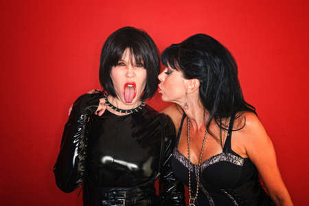 lesbian girls: A dominatrix woman sticks her tongue out while the another tries to kiss her.
