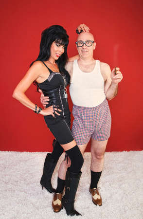 A playful dominatrix and her client pose for the camera.