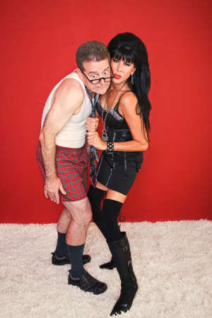 A beautiful dominatrix pulls on her fearful clients necktie.