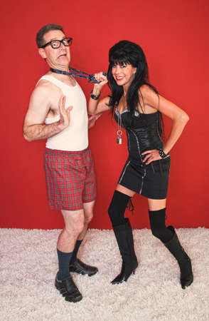 A man in a tie poses fearfully with an excited dominatrix woman. Stock Photo