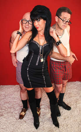 An eager dominatrix woman poses with two of her clients behind her. Stock Photo