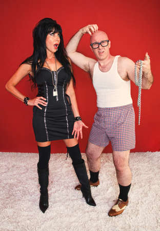 beautiful bdsm: Annoyed dominatrix woman waits as her client poses in confusion. Stock Photo