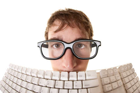 Young Caucasian man hides behind a computer keyboard over white background Stock Photo