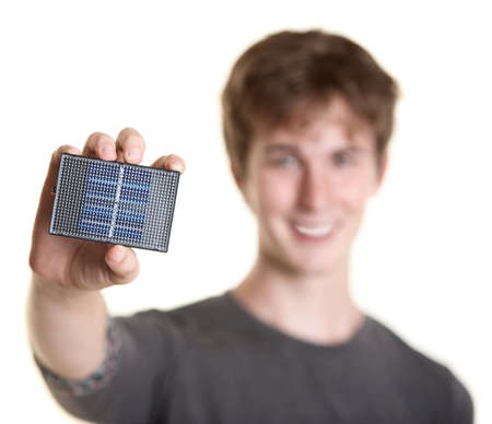 Smiling young man holds solar panel over white background photo