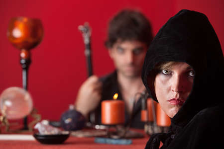 sceptre: Serious witch stares with wizard holding sceptre over red background
