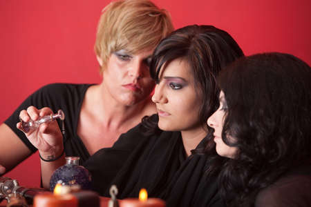 threesome: Woman pours potion into bottle over red background Stock Photo