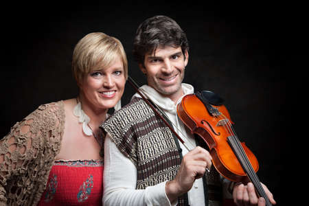 Beautiful lady with handsome man with violin smile over black background photo