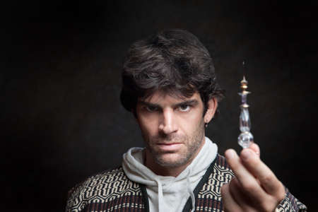 Serious young Caucasian wizard holds potion bottle photo