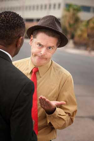 Caucasian businessman with open hand in front of African-American male