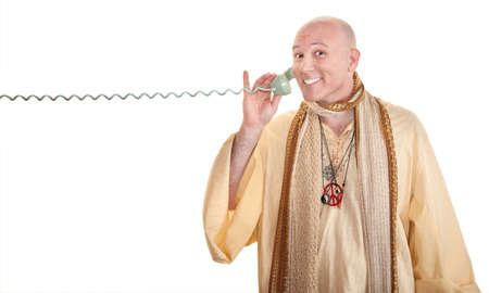 Bald Caucasian monk grins on phone call over white background photo