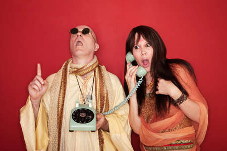 Shocked Caucasian on phone call while bald monk points index finger upward toward heaven photo