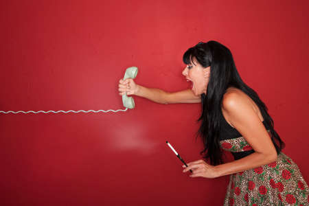 Frustrated Caucasian woman yells on phone call over maroon background photo