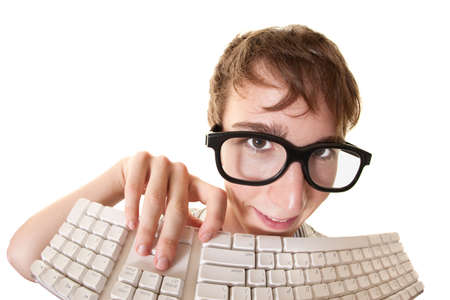 technophobe: Teen smiles behind a computer keyboard over white background Stock Photo