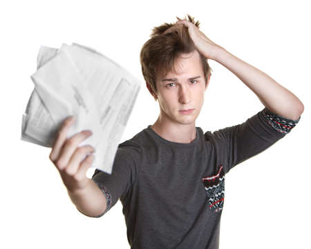 bills: Unhappy young Caucasian man holds documents over white background