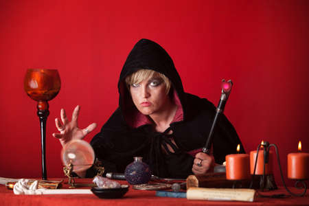 sceptre: Witch holding sceptre gazes crystal ball over red background Stock Photo