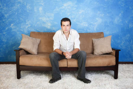 clench: Bored young Caucasian man with hands clasped relaxes on sofa Stock Photo