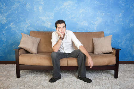 Bored young Caucasian man sits on sofa with hand on face