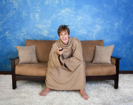 barefoot man: Smiling Caucasian teen in brown bathrobe watches television  Stock Photo