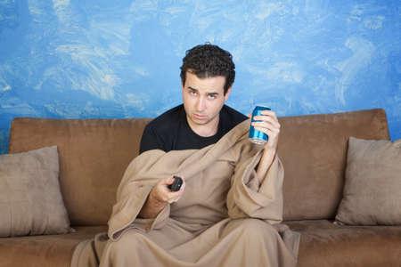 lata de refresco: Aburrido hombre de raza cauc�sica con lata de refresco y el control remoto se sienta en el sof� Foto de archivo