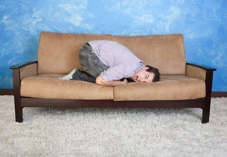 curledup: Frustrated young man on sofa
