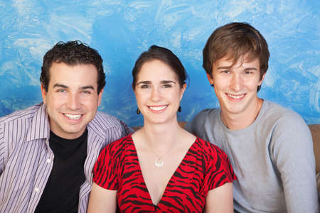 threesome: Three happy friends smile over blue background