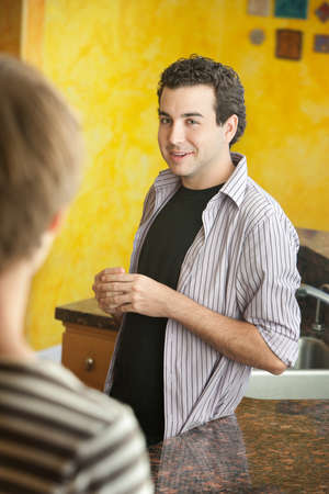 chitchat: Two friends chit chat in kitchen a Stock Photo