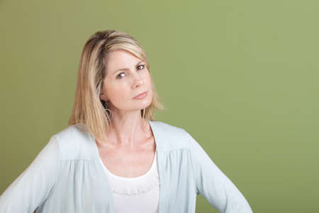 skeptic: Suspicious mature Caucasian woman over green background Stock Photo