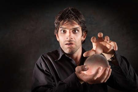 foretell: Fortuneteller gazes crystal ball over maroon background