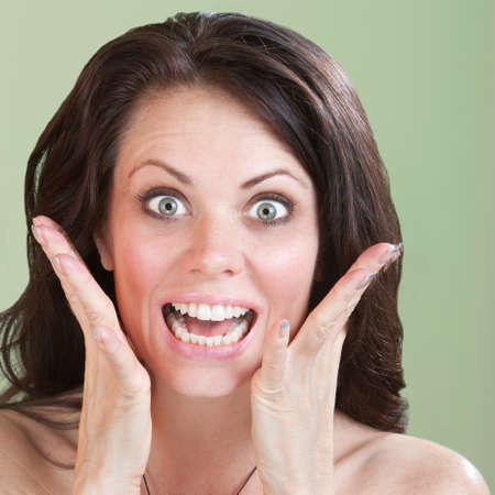 raised eyebrows: Excited Caucasian woman with raised eyebrows over green background Stock Photo