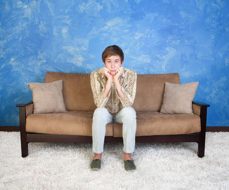 man couch: Confused or bored teen with hands on chin sits alone