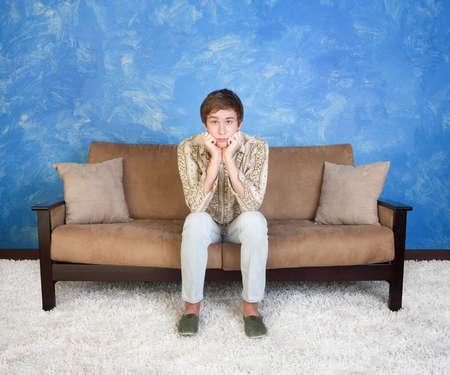 mann couch: Verwirrt oder gelangweilt Teenager mit den H�nden am Kinn sitzt allein Lizenzfreie Bilder