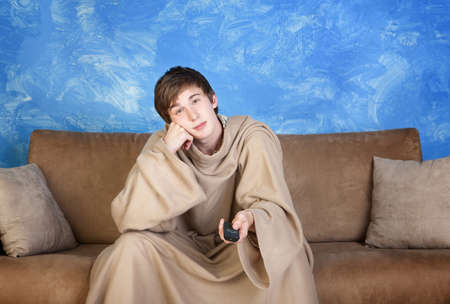 face centered: Bored young man in bathrobe and remote control