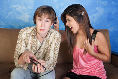 Beautiful young woman yells at boy with headphones Stock Photo - 10734566