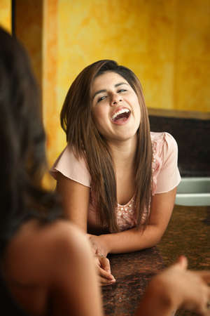 Hispanic girl with friend laughs out loud Stock Photo - 10734556