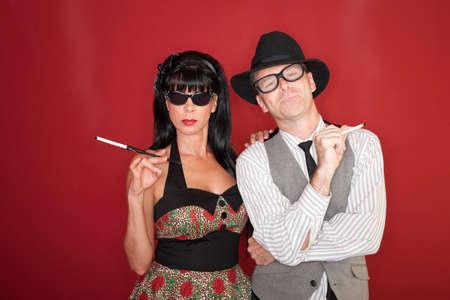 Retro-styled Caucasian couple smokes cigarettes over maroon background photo