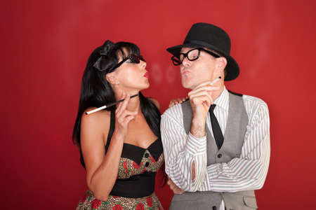 Retro-style couple blow smoke rings at each other photo