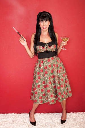 toed: Sad Caucasian woman with martini and cigarette over red background