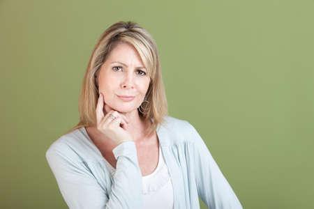 녹색 배경 위에 턱에 손가락으로 회의적인 성숙한 여자
