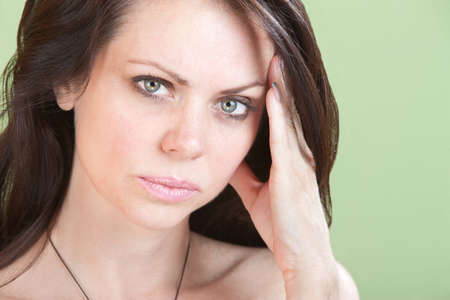 sinusitis: Young woman over green background holds side of her head.